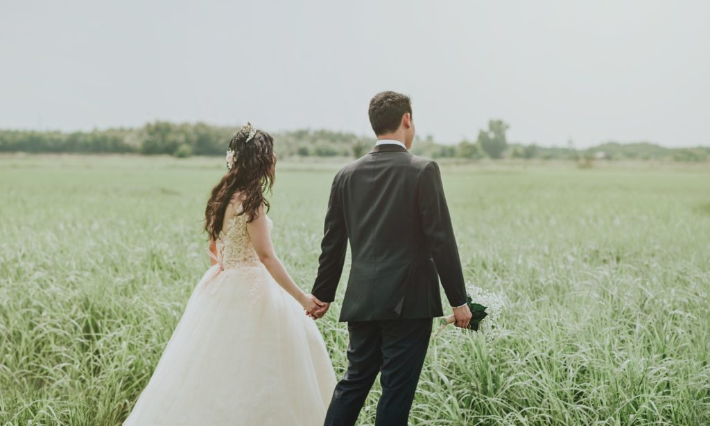 woman-in-white-wedding-dress-holding-hand-to-man-in-black-752842