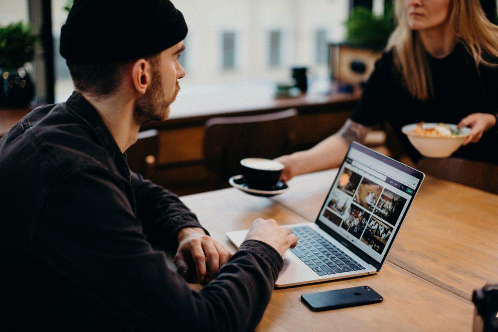 man-wearing-black-jacket-using-laptop-computer-sitting-3584926