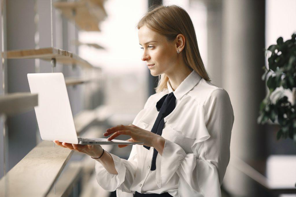 focused-worker-using-laptop-in-office-lobby-4173263
