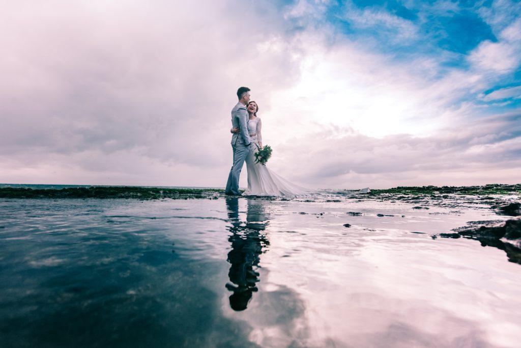 man-in-gray-dress-suit-jacket-embraces-woman-wearing-wedding-931796