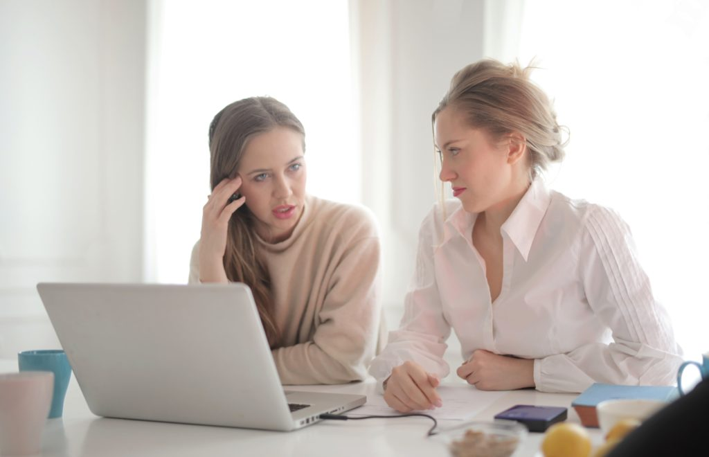 thoughtful-businesswomen-discussing-problems-in-bright-3831888