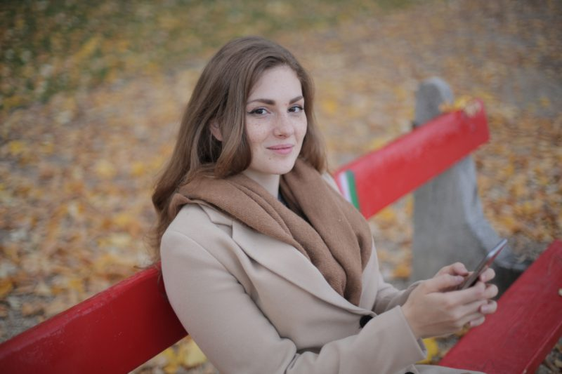 woman-in-gray-coat-sitting-on-red-bench-3776452